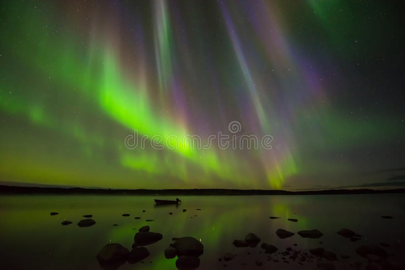 Colors of Northern Lights. Multi-colored aurora borealis hovering over a rocky lake royalty free stock image