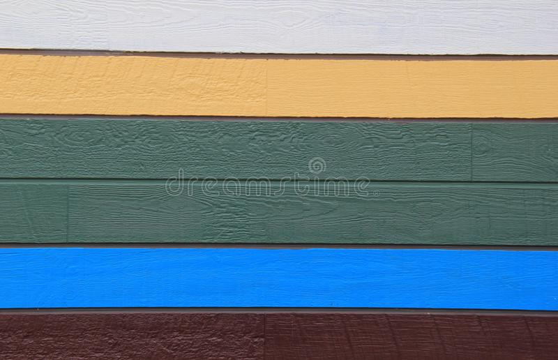 Exterior siding of building with colorful paint on each wooden slat. Colors of white, yellow, green, blue, and brown painted on exterior wall of building royalty free stock image