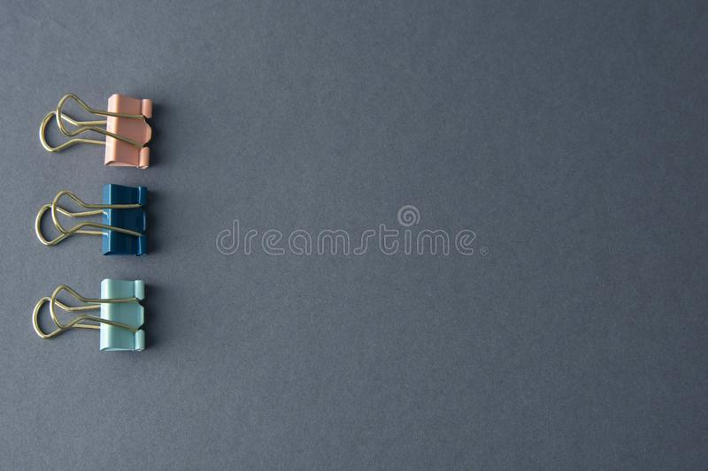 Colorul binder clips isolated on grey background, work space, work table, copy space. Colorul binder clips isolated on grey background, work space, work table royalty free stock photo