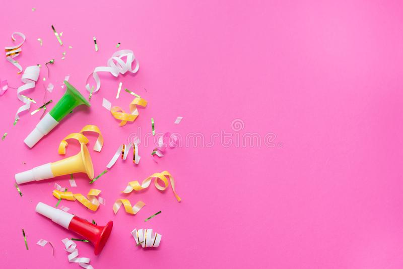 Colorul party streamers on pink background. Celebration concept. Flat lay stock images