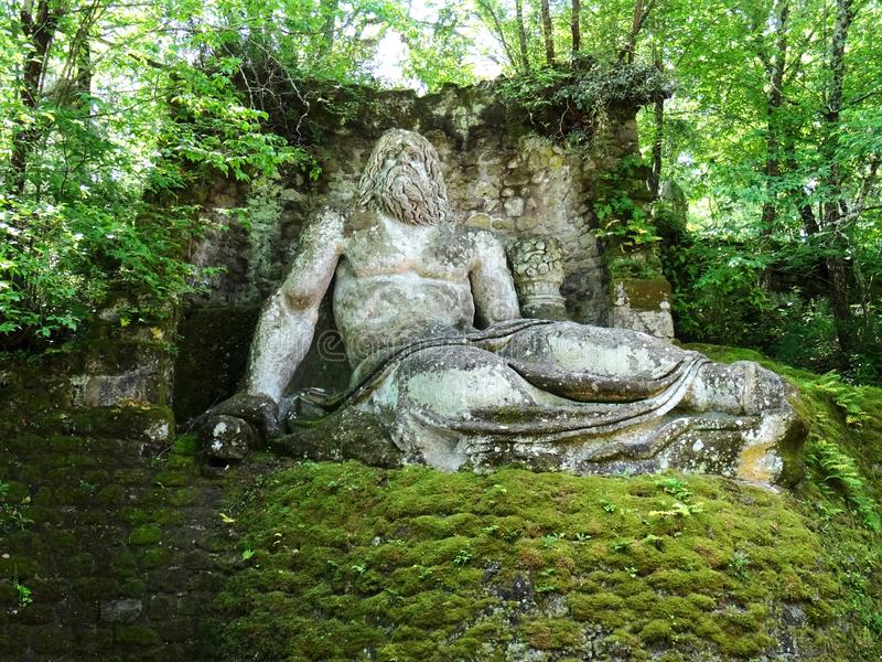 Colossal statue in the forest of Bomarzo. Italy. Colossal Mannerist Renaissance statue of Neptune. 16th Century. Bomarzo. Lacio. Italy royalty free stock images