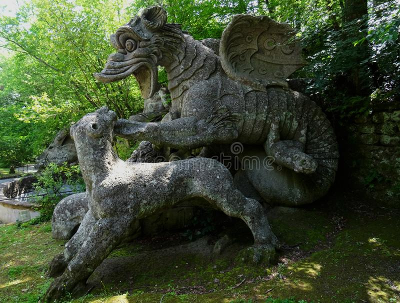Colossal statue in the forest of Bomarzo. Italy. Colossal Mannerist Renaisance statue of dragon hunting a wolf. 16th Century. Bomarzo. Italy royalty free stock photography