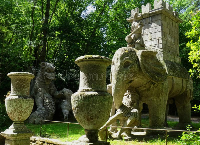 Colossal statue in the forest of Bomarzo. Italy. Colossal Mannerist Renaissance statue of Elephant and Castle, dragon in the background. 16th Century. Bomarzo royalty free stock photo