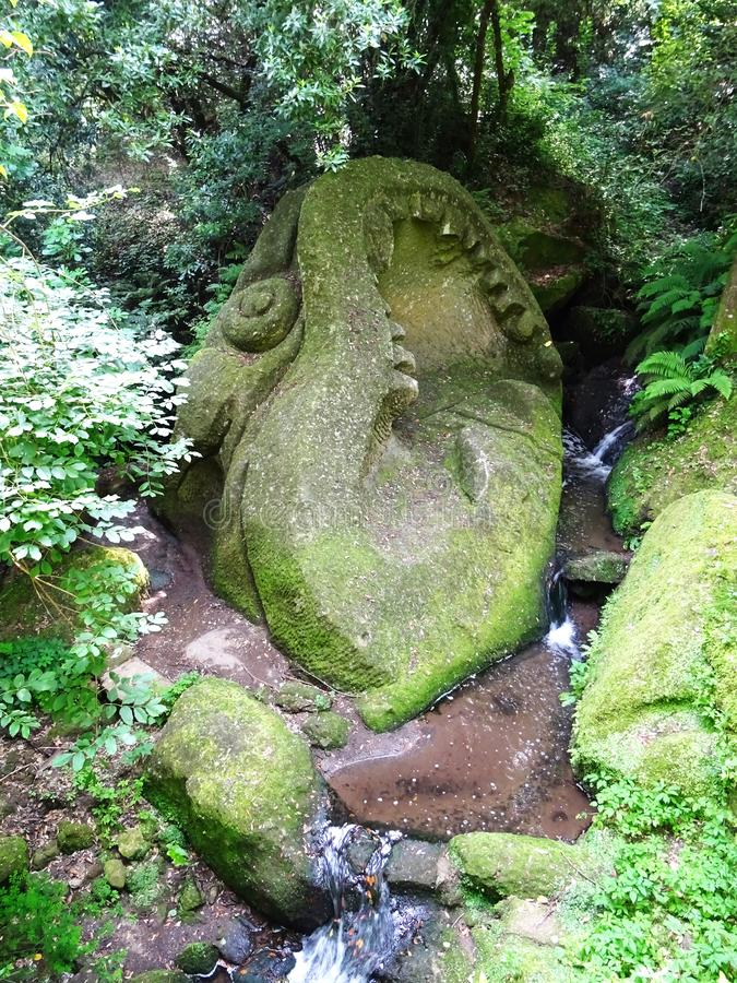Colossal statue of whale in the forest of Bomarzo. Italy. Colossal Mannerist Renaissance statue. Head of whale surfacing from the stream. Bomarzo. Lacio. Italy stock image