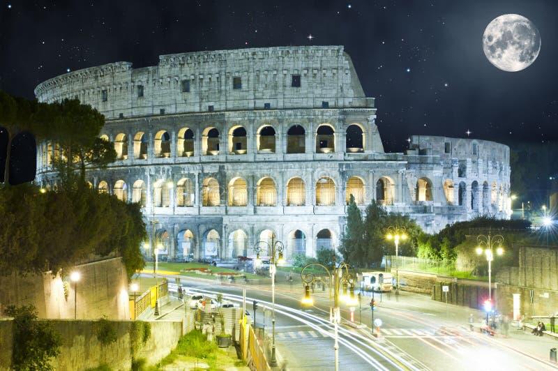 Colosseum på natten, Rome, Italien med den enorma månen arkivbilder