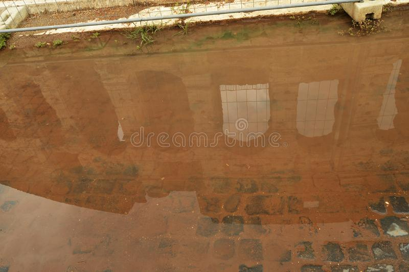 The Colosseum is reflected in a puddle with a brown background, unusual foreshortening sights of Rome Italy.  royalty free stock photos