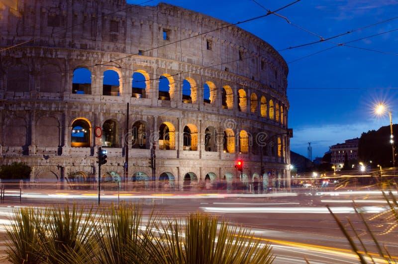 Colosseum in Rome, Italië bij nacht met verkeer die pa's wegschieten royalty-vrije stock fotografie