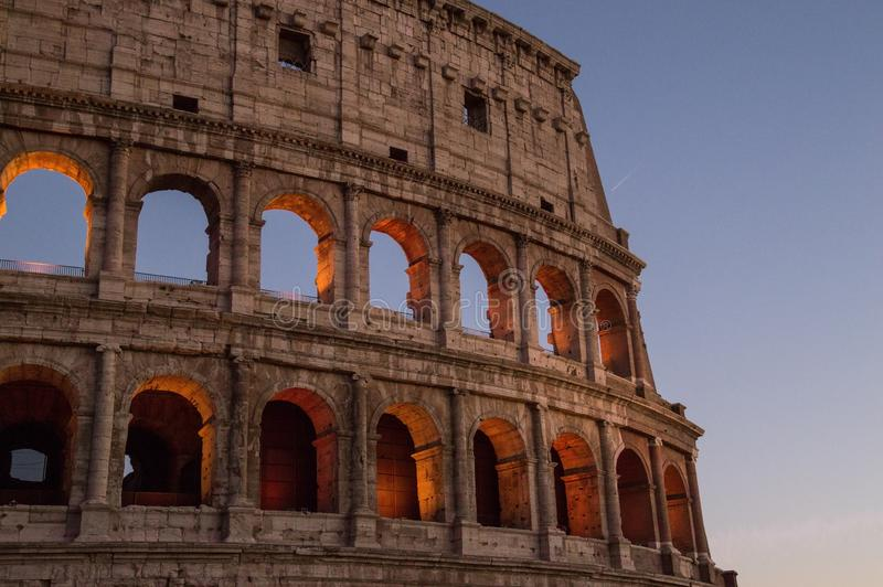 Colosseum, Rome, Italy. The outer wall of the evening coliseum. Arched openings are highlighted in orange backlighting. stock photos