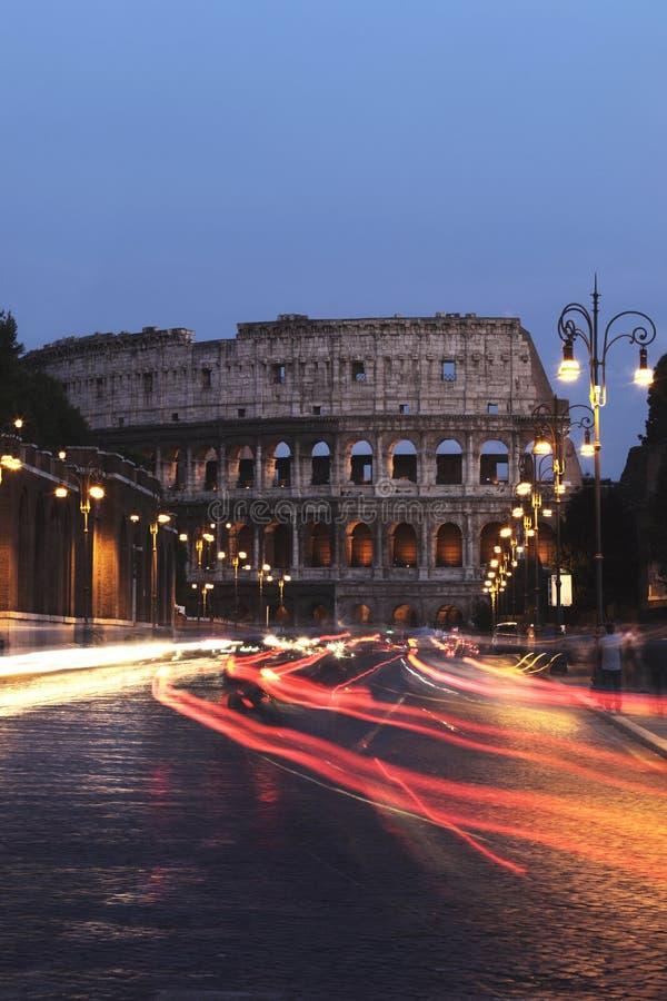 Colosseum y coches en la noche, Roma foto de archivo