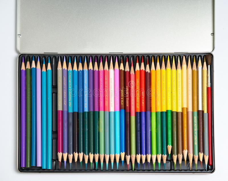 Colour pencils in aluminium box on isolated white background stock photography