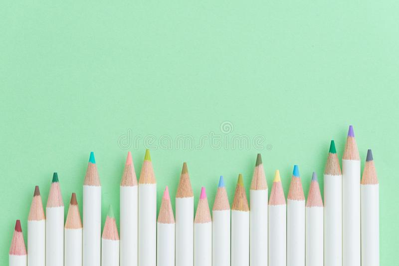 Colour pencils on pastel green paper background with copy space stock photos