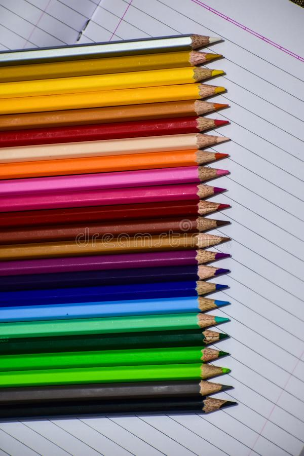 Colour pencils on white notebook royalty free stock image
