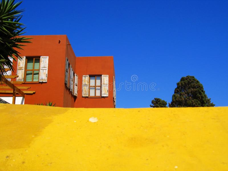 Colour trilogy with dominant yellow. Colour trilogy with orange painted house, dominant yellow wall and clear blue sky in the background, taken in spring time royalty free stock images