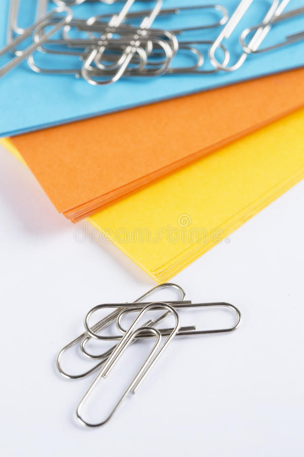 Coloured cardboard with paperclips on a white table stock photography