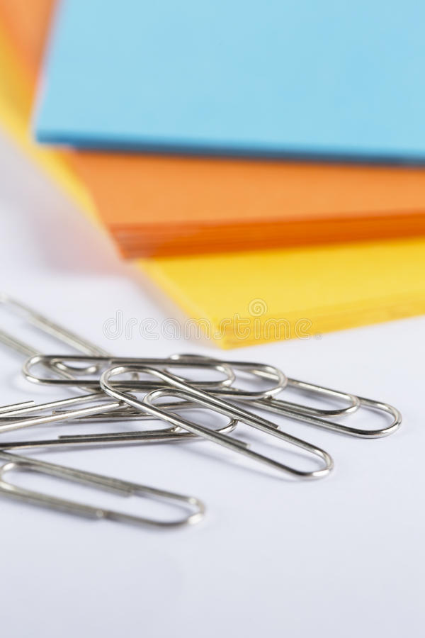 Coloured cardboard with paperclips on a white table stock image