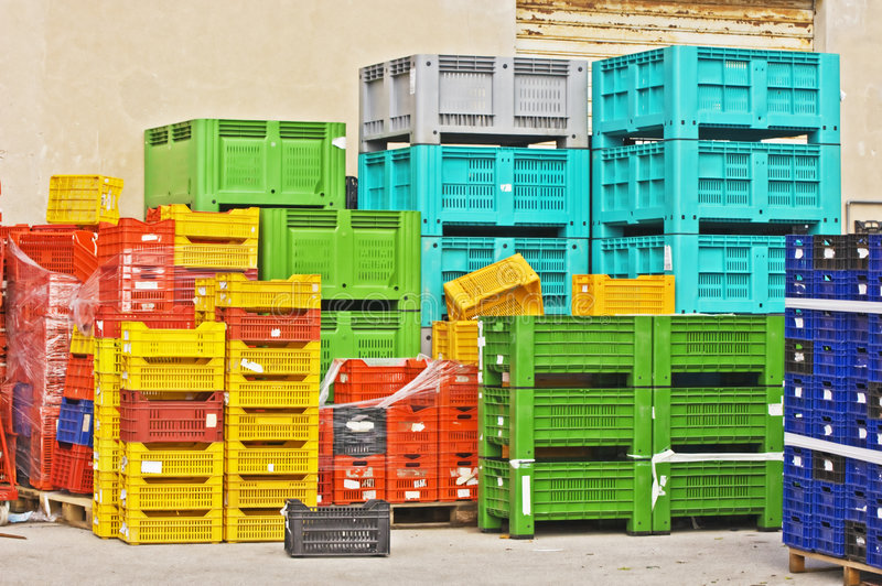 Coloured crates. Coloured stacks of fruits and vegetable crates in a storehouse royalty free stock images