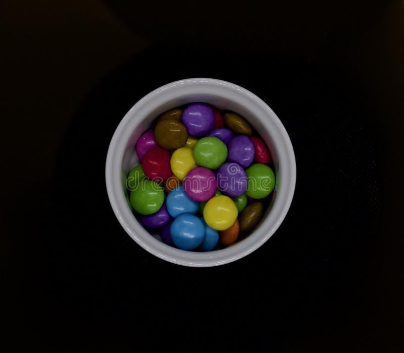 Coloured cukierki w białym garnku przeciw czarnemu tłu obraz stock
