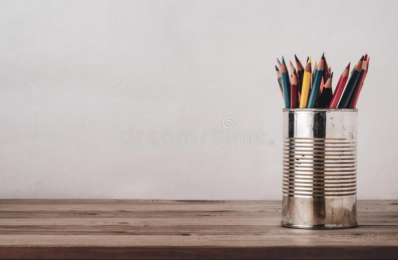 Coloured Drawing Pencils in Metal Tin on Wood Plank Desk stock images