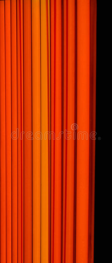 Coloured fluorescent lamp. Orange coloured fluorescent lamp on a wall royalty free stock images