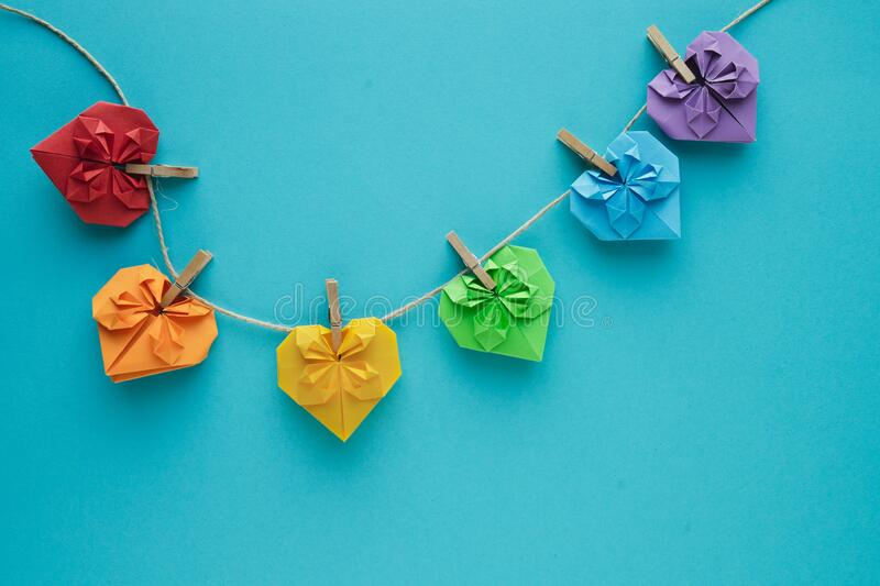 Coloured hearts hung on rope with wooden clips on a blue background. Copy space. Valentine`s Day concept. LGTB gay concept royalty free stock photography