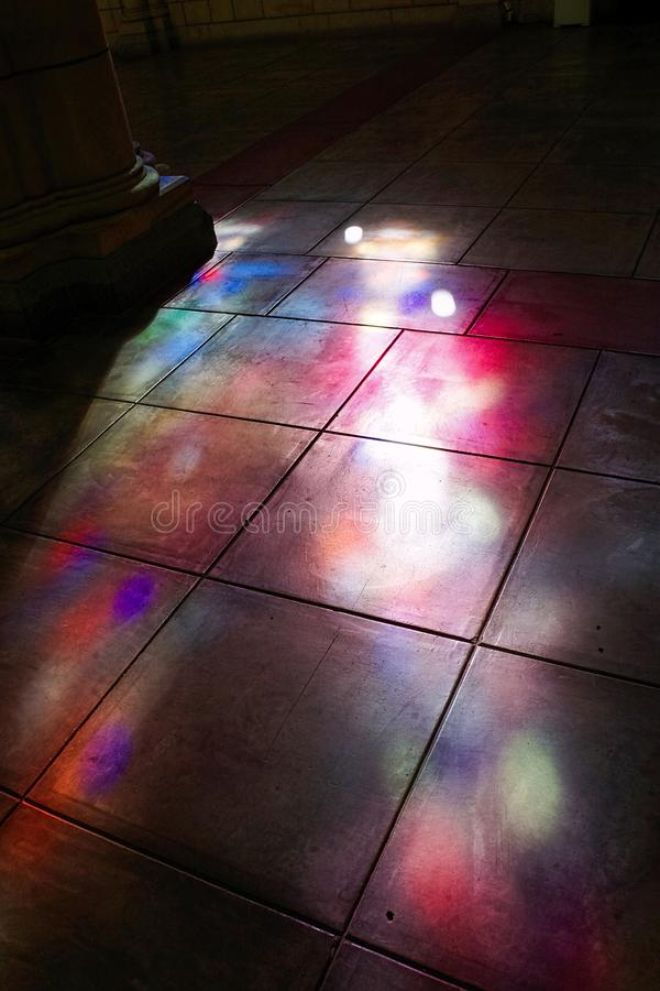Coloured light cast between colums by stained glass windows. Beautiful coloured light cast by stained glass church windows onto the flagstone floor. Negative stock photo