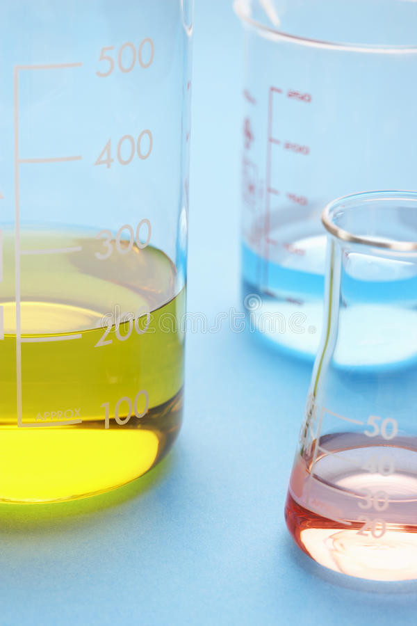 Coloured liquids in beakers close-up royalty free stock images