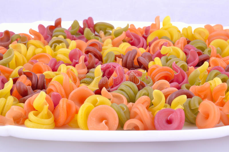 Coloured macaroni before cooking stock photos
