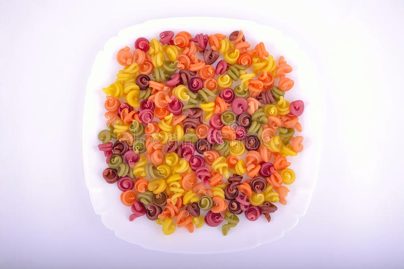 Coloured macaroni at plate royalty free stock images