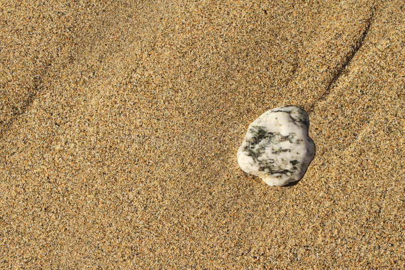 Coloured pebble on the sand. Grey and white pebble on the bright Summer sand stock photo