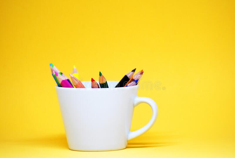 Coloured pencil or colorful Crayon for drawing on the white cup isolated with yellow pastel background Back to school concept royalty free stock photo