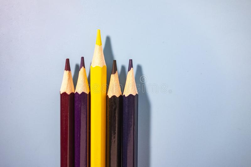 Coloured pencils arranged neatly. In a blue background stock images