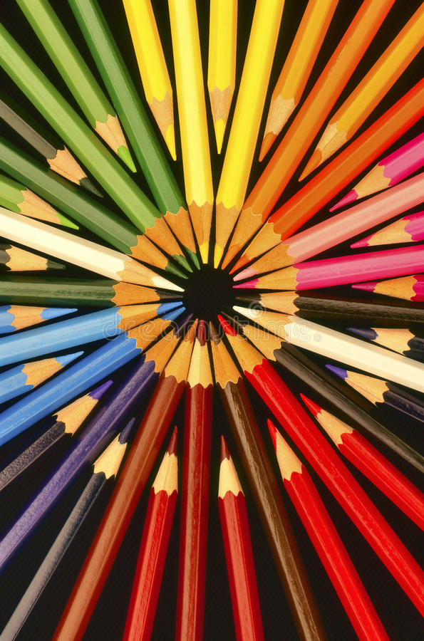 Coloured Pencils circles. A circular pattern of multi coloured pencils, on a black background royalty free stock photography