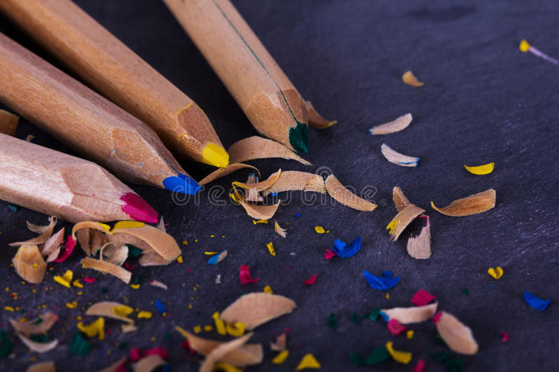Coloured pencils and shavings against a black background royalty free stock images
