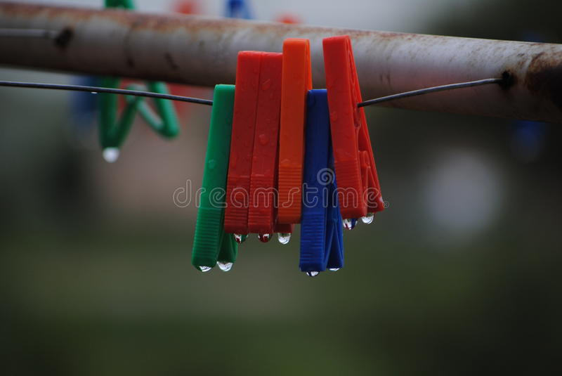 Coloured plastic pegs on a washing line. With rain water dripping on them stock image