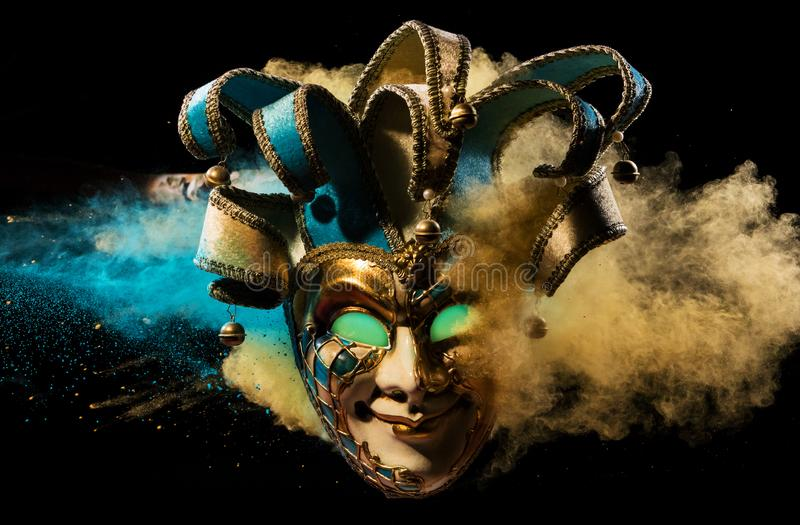 Coloured powder explosion with Venice mask stock images