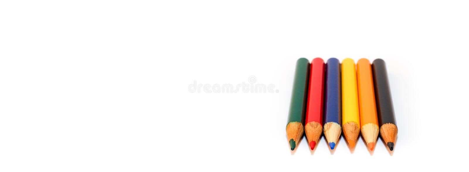 Coloured small pencils in colours green, red, blue, yellow, orange and black isolated on a wide white background. Coloured small pencils in colours green, red stock image