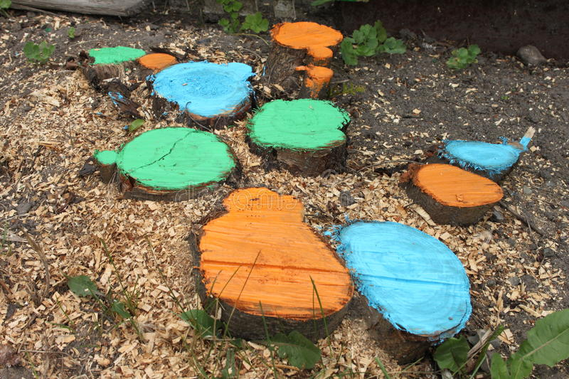 Coloured stubs with grass and sawdusts on a ground in a dacha garden stock image