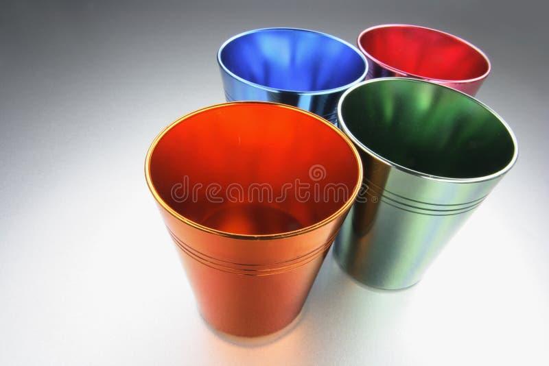 Coloured Tin Cups. On Dark Silver Grey Background stock photos