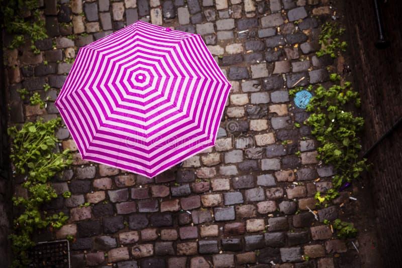 Coloured umbrella on alleyway. Unrecognizable female under umbrella walking on paved street stock image
