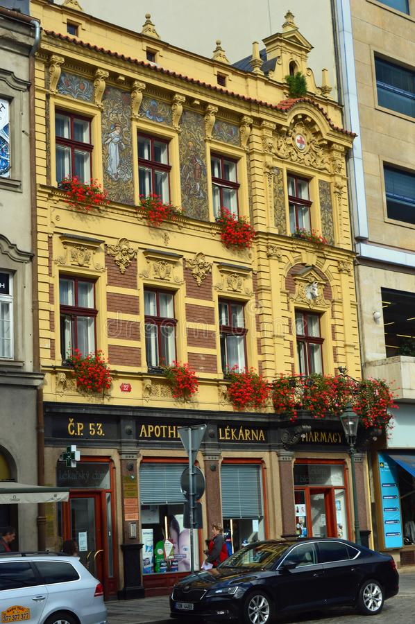 Colourful architectural detail Plzen Czech Republic. Pilsen. Yellow painted facade with red flower above an old fashioned apothecary shop royalty free stock photos