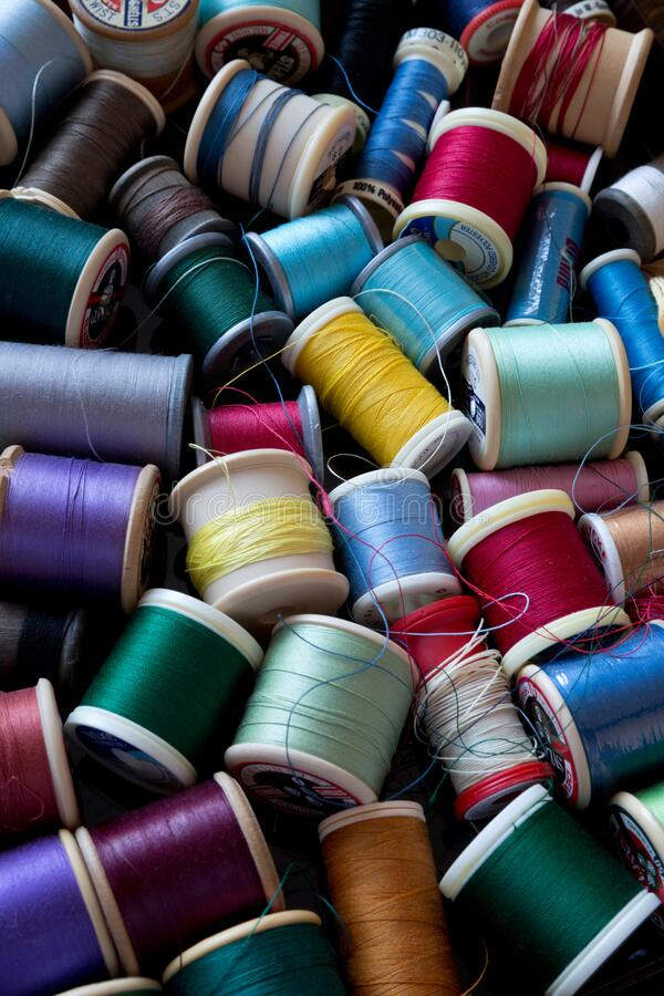Colourful assortment of cotton reels. Assortment of cotton reels in various colours with loose threads viewed from above stock photography