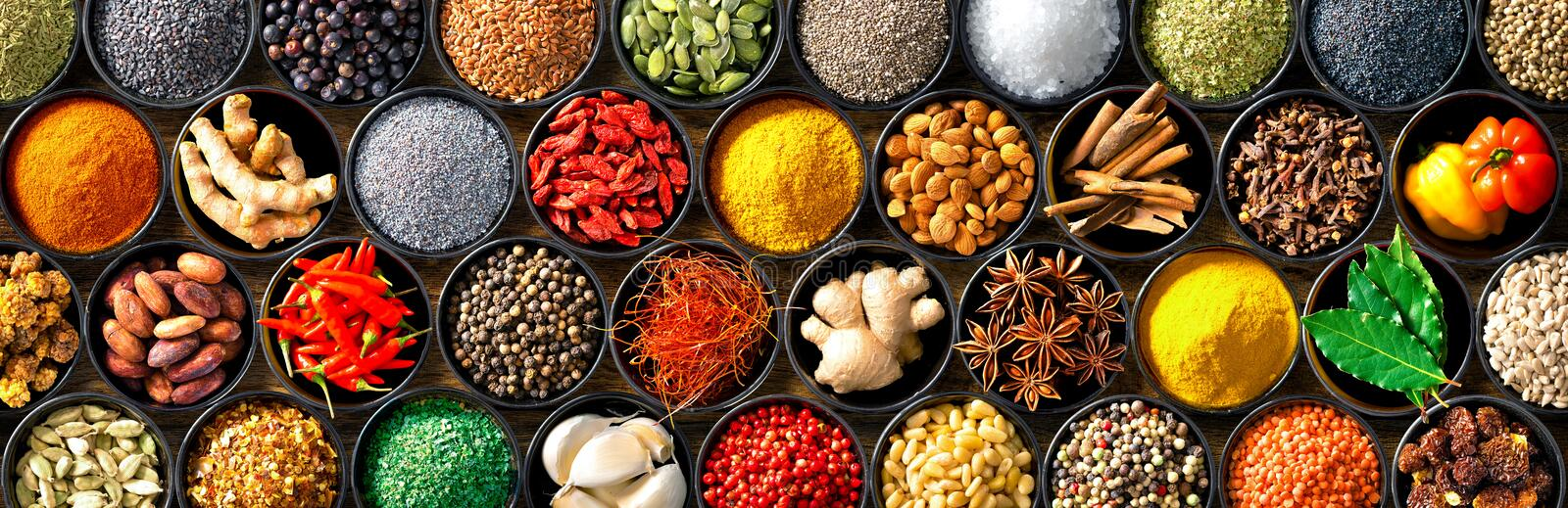 Colourful background from various herbs and spices for cooking in bowls stock image