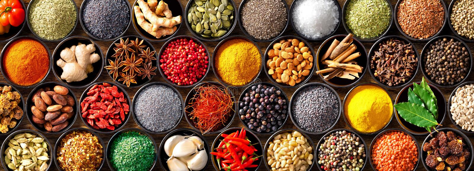 Colourful background from various herbs and spices for cooking in bowls royalty free stock images