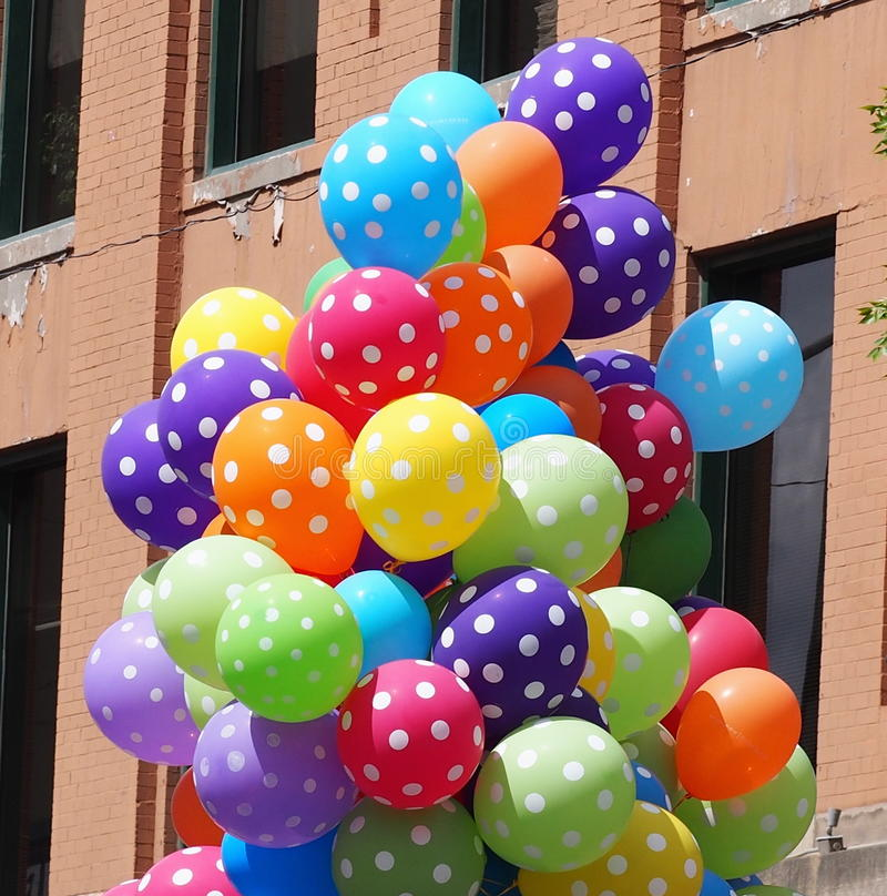 Colourful Balloons. A bunch of colourful balloons against a brick wall background stock image