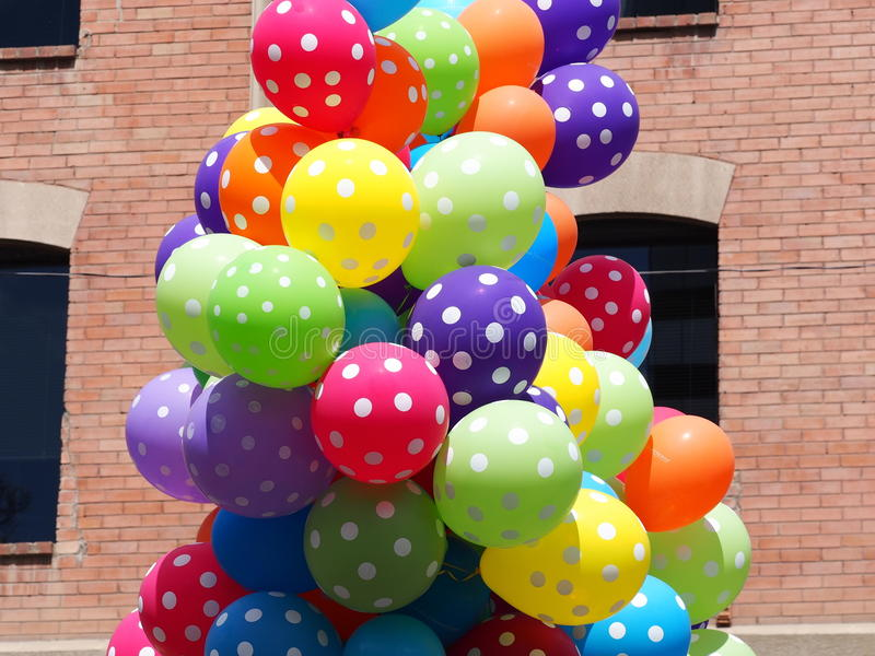 Colourful Balloons. A bunch of colourful balloons against a brick wall background royalty free stock image