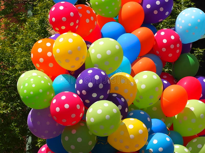 Colourful Balloons. A bunch of colourful balloons against a green leafy background stock image