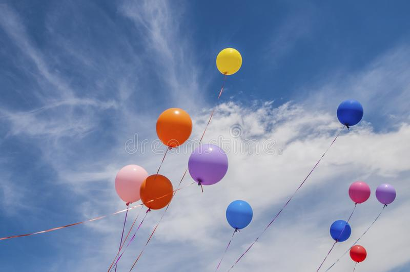 Colourful balloons floating in blue sky royalty free stock images