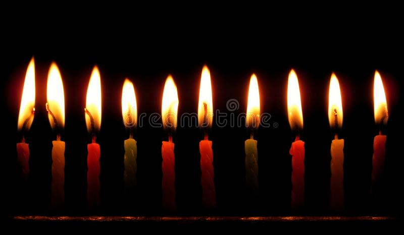 Colourful birthday candles Burning against black background stock image