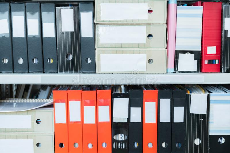 Colourful blank blind folders with files in the shelf. Archival, stacks of documents at the office or library. Physical document royalty free stock images