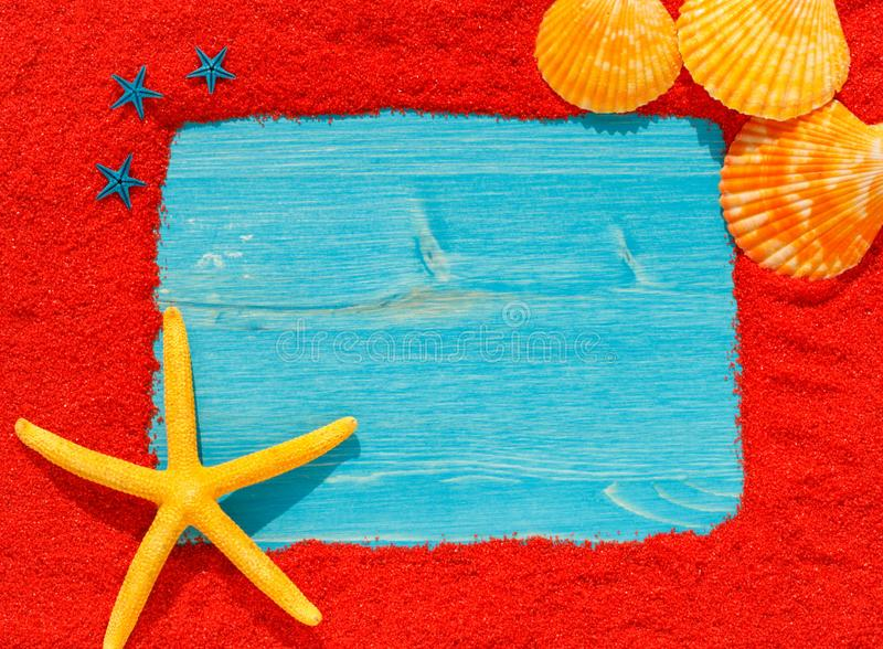 Colourful bright frame from red sand with a yellow starfish. Blue small starfishes and three orange seashells. Blue wooden empty card royalty free stock photo